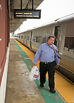 During evening rush hour, commuter with tie flying leaves train and walks on elevated platform of Merrick train station of Babylon branch, after MTA Metropolitan Transit Authority and Long Island Rail Road union talks deadlock, with potential LIRR strike looming just days ahead.