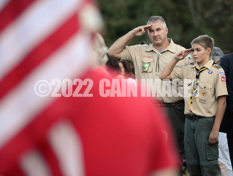 LOWER MAKEFIELD, PA -  SEPTEMBER 11:  Greg Rimensnyder (left) and Matthew Rimensnyder salute at the start of the Garden of Reflection 9/11 Memorial service September 11, 2013 in Lower Makefield, Pennsylvania. (Photo by William Thomas Cain/Cain Images)