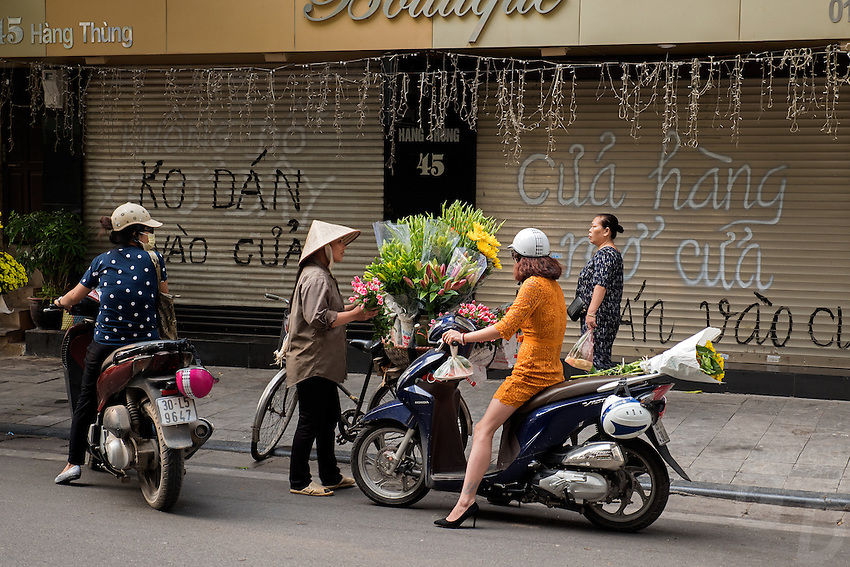 A early morning flower vendor selling flowers to a sexy Motorbike Girl. Hanoi, the capital of Vietnam, is known for its centuries-old architecture and a rich culture with Southeast Asian, Chinese and French influences. At its heart is the chaotic Old Quarter, where the narrow streets are roughly arranged by trade. There are many little temples, including Bach Ma, honoring a legendary horse, plus Đồng Xuân Market, selling household goods and street food.