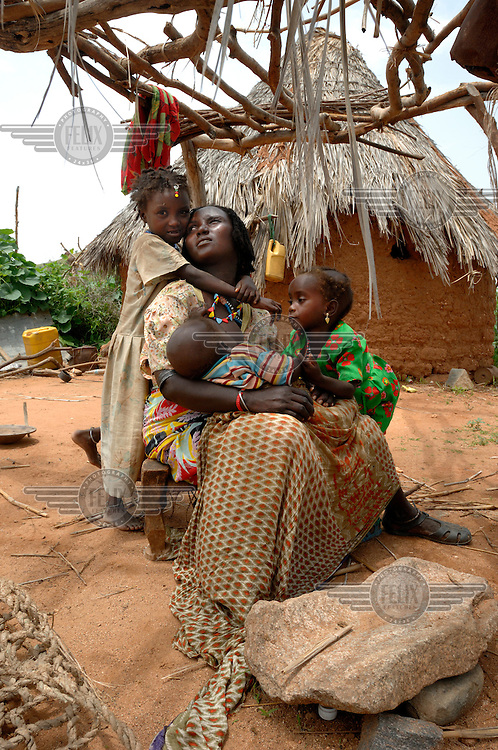 A woman and her children sit outside their home in Gulul. ..