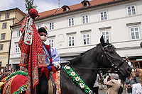 Participant in the procession on his Horse, drinking the wine the Moravian women serve the men in the procession. <br /> <br /> The Ride of the Kings takes place during the spring, as a part of the Pentecost traditions, in the towns of Hluk and Kunovice and the villages of Skoronice and Vlčnov. A group of young men ride through a Prague in a ceremonial procession. The ride is headed by chanters, followed by pageboys with unsheathed sabres who guard the King &ndash; a young boy with his face partially covered, holding a rose in his mouth &ndash; and the rest of the royal cavalcade. The King and pageboys are dressed in women&rsquo;s ceremonial costumes, while the other riders are dressed as men. The entourage rides on decorated horses, stopping to chant short rhymes that comment humorously on the character and conduct of spectators. The chanters receive donations for their performance, placed either in a money box or directly into the riders&rsquo; boots. The King&rsquo;s retinue returns home after a few hours of riding, and celebrates in the evening at the house of the King with a small feast, music and dancing. The practices and responsibilities of the Ride of the Kings are transmitted from generation to generation. The traditional paper decorations for the horses and the ceremonial costumes, in particular, are made by women and girls familiar with the processes, colour patterns and shapes specific to each village.
