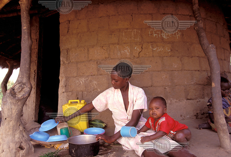 © Caroline Penn / Panos Pictures..Near Soroti, UGANDA. 07/1999..16 year old girl cooking for her 3 month old baby in the village of Dokoro.