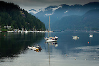 Yachts relected in the bay. Deep Cove Bay with clouds above the mountains over Mount Seymour provincial park. Deep Cove, Burrard Inlet, Vancouver, British Columbia, Canada.
