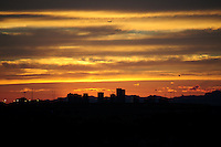 Tempe, Arizona. The sunset forms a beautiful and rich background that highlights the the Downtown Phoenix skyline. The image was zoomed in from the pedestrian bridge of the lake. The artificial lake is a reservoir on a segment of the currently dry riverbed of the Salt River. The new dam will be a cost-effective solution expected to last for decades. The construction is called Town Lake Western Dam Replacement Project. Photo by Eduardo Barraza © 2015