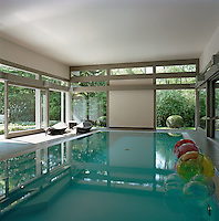 Coloured balls float on the surface of the indoor swimming pool which has large windows opening to the garden
