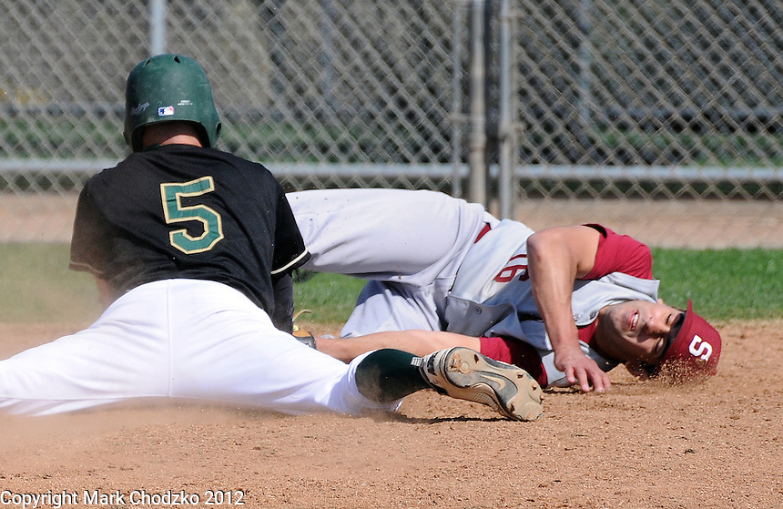 Baseball runner slides head first at home knocking pitcher over covering the plate on a past ball.