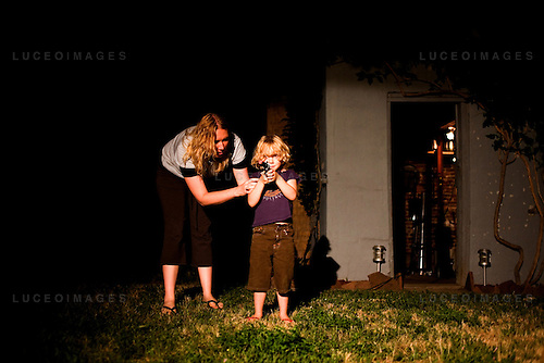 Asher Demoney, 4, playing with his new Indiana Jones gun in his Denver backyard.  Portraiture and documentary mix.
