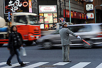 A traffic warden directs traffic on a busy road in Tokyo, Japan..19 Feb 2010