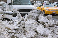 Big, dirty piles of snow and ice, collected over numerous snow storms this season, on the street in the Chelsea neighborhood of New York on Wednesday, February 12, 2014. Yet another storm, this one a Nor'easter, is expected to contribute to those piles around midnight after traveling up from the south and will dump another 4 to 12 inches of snow. (© Richard B. Levine)