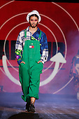 A male model wearing oversized green overalls by Tommy Hilfiger