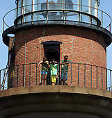 Aquinnah, MA - August 27, 2009 -- Malia, 11, and Sasha, 8, Obama, with an unidentified boy, peer from Gay Head Lighthouse, first used in 1799, in Aquinnah on Martha's Vineyard, Mass. Thursday, August 27, 2009. The Obama's visited the lighthouse with President Obama's brother-in-law Konrad Ng and Obama's friend Eric Whitaker and his family after a bike ride in Aquinnah..Credit: Vincent DeWitt - Pool via CNP