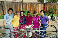 DIVERSE GROUP OF CHILDREN ON A MERRY-GO-ROUND IN THE PARK. MULTI-ETHNIC GROUP OF KIDS. OAKLAND CALIFORNIA USA.
