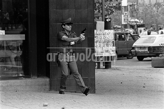 Un guardia de un banco amedentra a alumnos del Colegio Latinoamericano que marcharon para conmemorar un ano del degollamiento de Parada y Guerrero asesinados po carabineros despues de ser secuestrados desde las puertas del  colegio el 29 de Marzo de 1985. Santiago Chile 31 Marzo 1986<br /> Forty years ago, on September 11, 1973, a military coup led by General Augusto Pinochet toppled the democratic socialist government of Chile. President Salvador Allende was killed during the  attack to seize  La Moneda presidential palace.  In the aftermath of the coup, a quarter of a million people were detained for their political beliefs, 3000 were killed or disappeared and many thousands were tortured.<br /> Some years later in 1981, while Pinochet ruled Chile with iron fist, a young photographer called Juan Carlos Caceres started to freelance in the streets of Santiago and the poblaciones or poor outskirts, showing the growing resistance against the dictatorship. For the next 10 years Caceres photographed every single protest and social movement fighting for the restoration of democracy. He knew that his camera was his only weapon, he knew that his fate was to register the daily violence and leave his images for the History.<br /> In this days Caceres is working to rescue and organize his collection of images in the project Imagenes de la Resistencia   . With support of some Chilean official institutions, thousands of negatives are digitalized and organized to set up the more complete visual heritage of this  violent period of Chile´s history.<br /> In a time when technology was not very friendly and communications were kind of basic, Juan Carlos Caceres and other photojournalist were always at the right place in the right moment defying the threats of the police. Their work is now  a visual heritage that documents and remind us the fight of Chilean people for democracy.