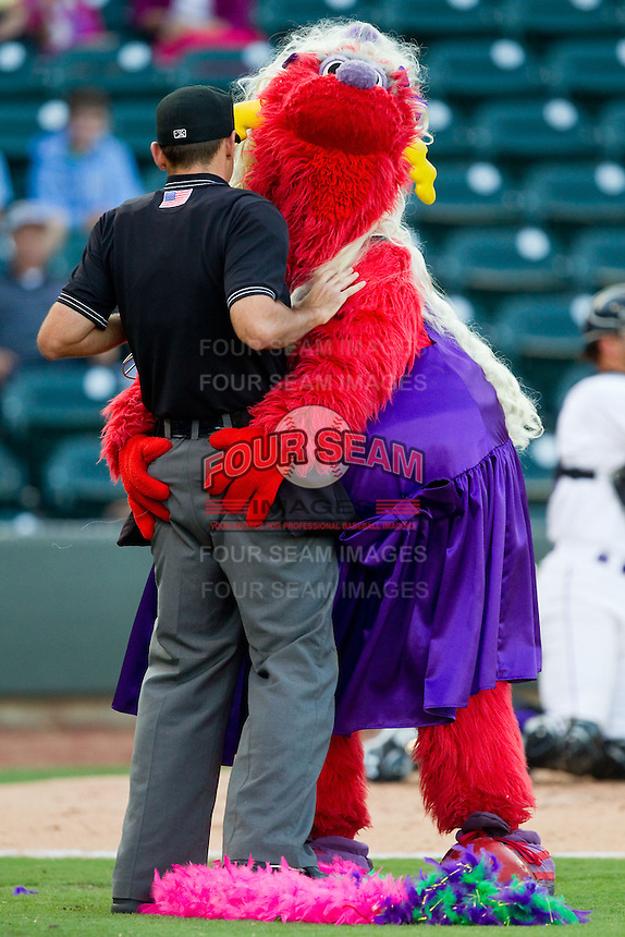 """Winston-Salem Dash mascot """"Bolt"""" entertains the crowd by dancing with home plate umpire Brian Miller between innings of the Carolina League game against the Salem Red Sox at BB&T Ballpark on August 15, 2013 in Winston-Salem, North Carolina.  The Red Sox defeated the Dash 2-1.  (Brian Westerholt/Four Seam Images)"""