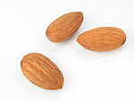 Closeup of three almonds, almond seeds isolated on white background