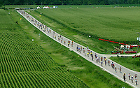RAGBRAI riders arrive to Kesley between lush corn fields.  The town of 80 residents welcomed the 10,000 to a main street full of antique tractors.