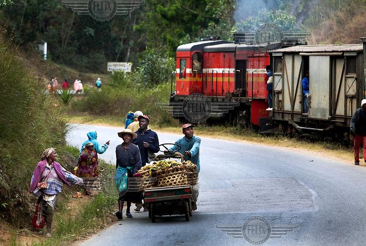A group of farmers push a cart, loaded with bananas, along a road to market. Beside the road a train runs between Fianarantsoa and Manakara.