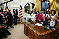 US President Donald J. Trump (C-R) delivers remarks during a signing ceremony for the bill, 'the Women's Suffrage Centennial Commemorative Coin Act', in the Oval Office of the White House in Washington, DC, USA, 25 November 2019. Trump signed 'H.R. 2423, the Women's Suffrage Centennial Commemorative Coin Act' - a bill directing the US Treasury to mint and issue up to four hundred thousand one-dollar silver coins honoring women that played a role in gathering support for the 19th Amendment.<br /> Credit: Michael Reynolds / Pool via CNP/AdMedia