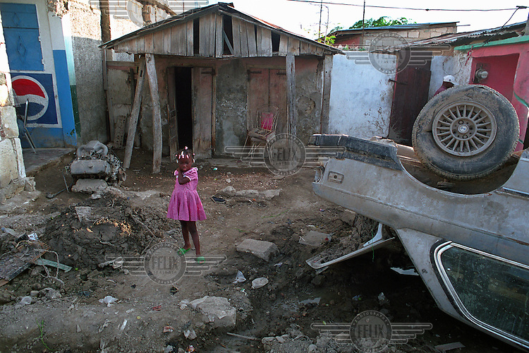A little girl in front of her house, next to an overturned car..Three weeks after tropical storm Jeanne hit Gonaives parts of the city are still flooded. Over 2700 people were reported dead or missing. Haiti is particularly vulnerable to flooding after heavy rainfall due to intense deforestation.