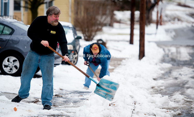 TORRINGTON, CT--- -122915JS03--Torrington residents Mike Tyrrell, left, and Thomas Re clear snow and ice from the sidewalk of their home on Scoville Street in Torrington on Tuesday. <br /> Jim Shannon Republican-American