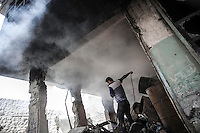 A Syrian civilian tries to put out the fire caused by a Syrian aircraft shelling as it targets a house buildings killing many civilians and injuring many others at the residential neighborhood of Zahraa in northeastern Aleppo. The Syrian army is carrying out aircraft shellings over residential areas throughout Aleppo City killing hundreds of civilians during the ongoing battle for the control of the city.