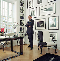 Portrait of John Demsey standing amongst his large collection of framed photographs in a corner of the large living room of his Manhattan town house