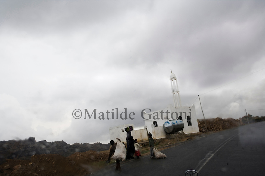Yemen - Family going back home after having collected water from a well down the hill. Yemen's economy depends heavily on oil production, and its government receives the vast majority of its revenue from oil taxes. Yet analysts predict that the country's petroleum output, which has declined over the last seven years, will fall to zero by 2017. The government has done little to plan for its post-oil future. Yemen's population, already the poorest on the Arabian peninsula and with an unemployment rate of 35%, is expected to double by 2035..The trends will exacerbate large and growing environmental problems, including the exhaustion of Yemen's groundwater resources. Given that a full 90% of the country's water is used for agriculture, this trend portends disaster..Sanaa's well are expected to dry out by 2015, partly due to illegal drilling, partly because 40% of the city's water is diverted for qat production, and partly because conservation rules are difficult to enforce. Only 20% of the houses receive water, the other 80% has to collect it from pumps and wells. 15% of the urban population only uses bottled water as its primary drinking water source and that is why Yemen has one of the highest world mortality rate, most of the diseases being related to water..