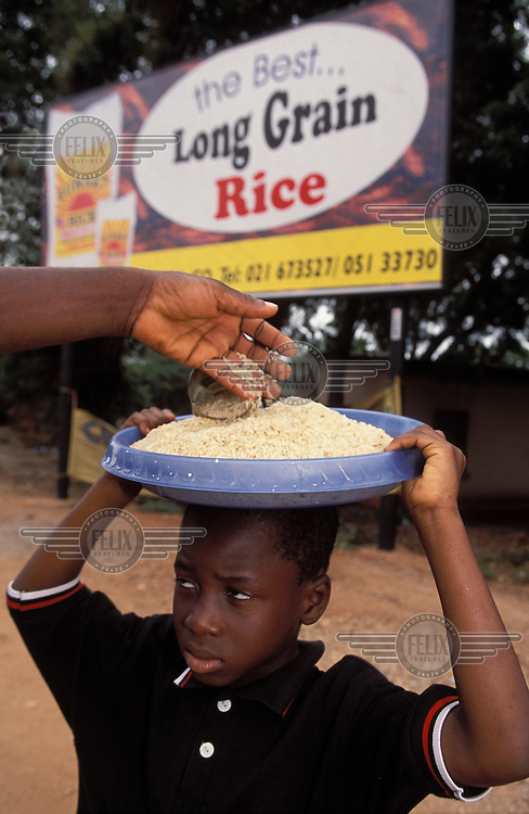A boy sells rice at a roadside in Accra.