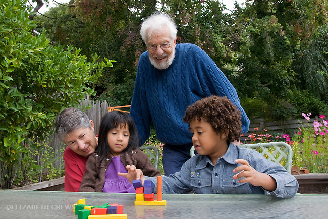 Berkeley CA Grandparents playing balancing block game with adopted Guatemalan granddaughter,four, and half African American grandson, five.  MR