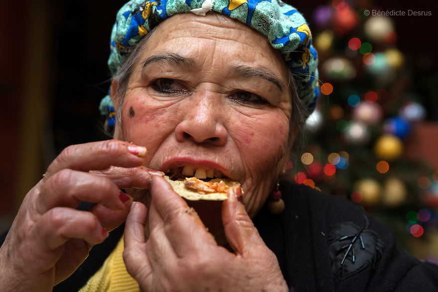 "Amalia, a resident of Casa Xochiquetzal, eats a ""tacos"" at the shelter in Mexico City, Mexico on December 11, 2008. Amalia, 66, is from Michoacán and came to Casa Xochiquetzal when it first opened its doors. She wears a wig and pads her bra. She is very animated; words and songs come easily to her. She has also suffered from schizophrenia for 22 years, but despite hearing voices, she works hard not to lose touch with reality. As a way of earning a little money, she gathers plastic bottles to recycle and also helps to sell clothes in a stand operated by her boyfriend of 31 years. Casa Xochiquetzal is a shelter for elderly sex workers in Mexico City. It gives the women refuge, food, health services, a space to learn about their human rights and courses to help them rediscover their self-confidence and deal with traumatic aspects of their lives. Casa Xochiquetzal provides a space to age with dignity for a group of vulnerable women who are often invisible to society at large. It is the only such shelter existing in Latin America. Photo by Bénédicte Desrus"