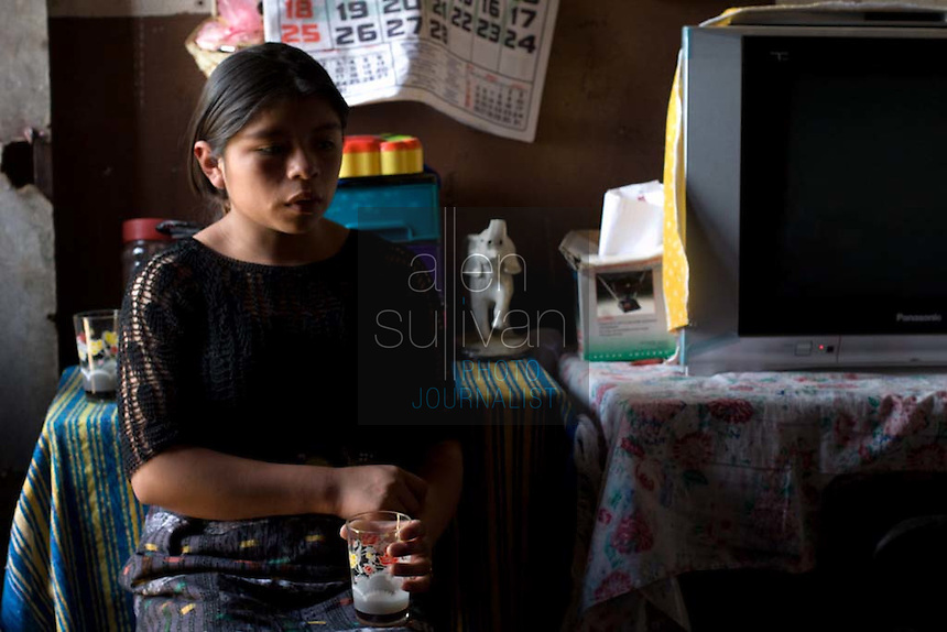 Maria, 16, sits in her friend Alma's home in Chimaltenango, Guatemala on Thursday, March 8, 2007. Maria works at Legumex, a vegetable and fruit company that exports to the United States. She injured her wrist on the job and couldn't work today.