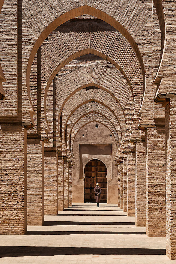 Traditional dressed man walks inside the Tinmal mosque, Morocco.