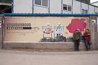 Men Standing and Talking next to real estate signage in Huinong, China.  © LAN