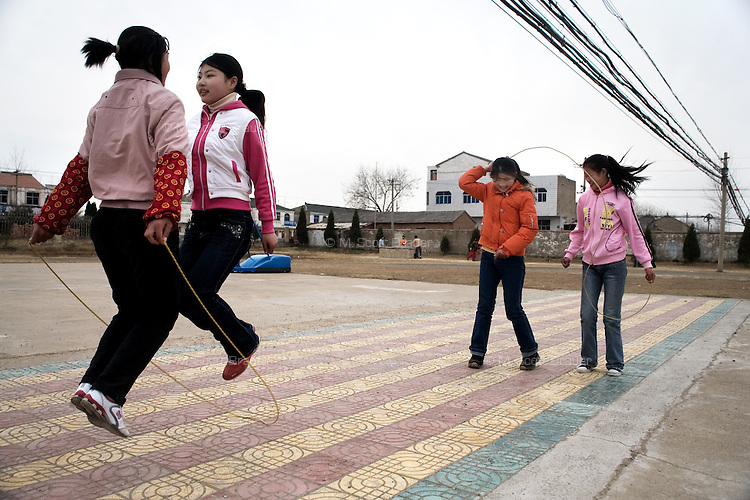 Girls jump rope during recess at Xiaoliji Middle School in Lianshui County, Jiangsu Province, China.  The Pfrang Association, a German charity based in Nanjing, China, sponsors a number of children in the school, providing money for boarding, food, clothing, school supplies, and other necessities to continue schooling.  The majority of children at this school come from poor farming families in rural Jiangsu Province, China.