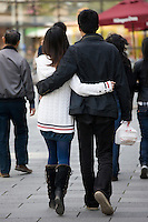 Modern couple walking arm-in-arm in redeveloped Xintiandi area, Huang Pi Road, Shanghai, China