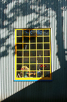 Yellow framed window in light and shadow, Granville Island, Vancouver, BC, Canada