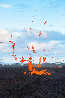 lava from Kilauea Volcano erupts from a fissure in Kapoho, near Pahoa, Puna, Big Island, Hawaii, USA, heaving hot lava spatter into the air, shimmering heat waves rising from magma underground distort the scene