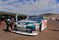 Nov. 13, 2009; Avondale, AZ, USA; A crew member makes an adjustment to the car of NASCAR Sprint Cup Series driver Dale Earnhardt Jr during practice for the Checker O'Reilly Auto Parts 500 at Phoenix International Raceway. Mandatory Credit: Mark J. Rebilas-