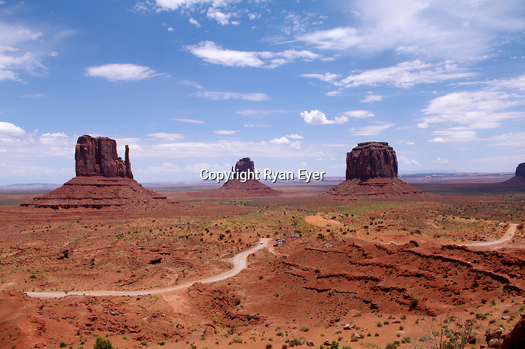 """MONUMENT VALLEY, UTAH - 9 July 2010 - Monument Valley panorama, taken from the Visitor Center and showing the """"Mittens"""" and the road which makes a loop-tour through the Park. The valley is part of the Colorado Plateau characterized by a cluster of vast sandstone buttes, the largest reaching 1,000 ft (300 m) above the valley floor. It is located on the southern border of the state of Utah with northern border of the state of Arizona.Picture: Ryan Eyer/Allied Picture Press"""