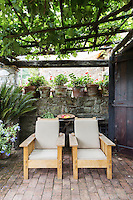The covered outdoor terrace with its vine covered roof and flower filled pots is a cool and relaxing space.
