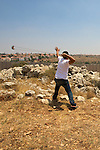 A Palestinian youth uses a slingshot to hurl stones at [unseen] Israeli soldiers on the other side of Israel's controversial separation barrier built on Palestinian land in the village of Ni'lin near Ramallah on 16/07/2010.