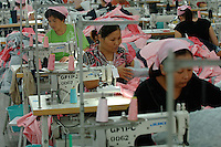 Female workers on production lines in a textile factory in Yixing city, in the Jiangsu Special Development Zone that makes clothes for western companies including Umbro Sports and New Balance.  Much of the world's textile manufacture has moved to China due to relatively low labor rates and high productivity and those clothes are almost exclusively made by women between 6 and 25 years old..23 Sep 2006