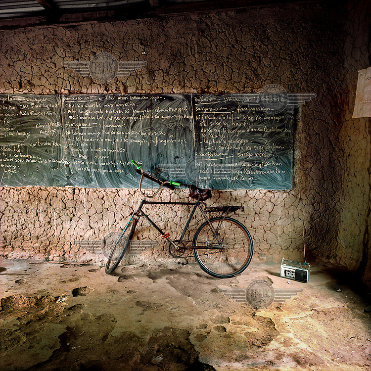 Bicycle propped against a blackboard and a radio in a school classroom.