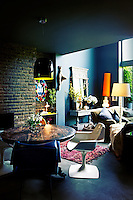 A blue open plan living room with an exposed brick wall. A black lamp hangs above a round dining table and retro chairs.