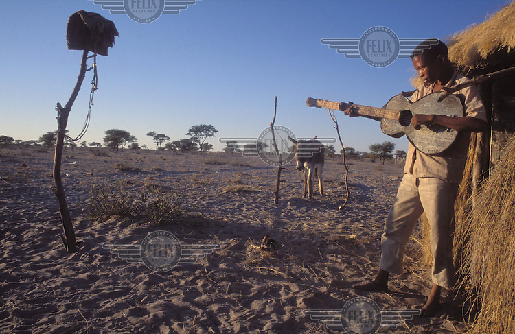 © Paul Weinberg / Panos Pictures..Bushmanland, Xade, Botswana...San Bushman playing his guitar, before the removals.