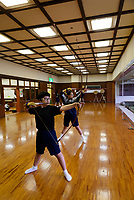 Local school children practicing archery, Kyudo Practice Hall, Miyakonojo, Miyazaki Prefecture, Japan, December 22, 2016. A handful of bowyers from the Kyushu city of Miyakonojo make over 90% of all the bows used in traditional Japanese archery. The bows are made from laminated bamboo and haze wood in process that consists of over 200 individual tasks. At over two meters from tip to tip the bows the longest used in the world.