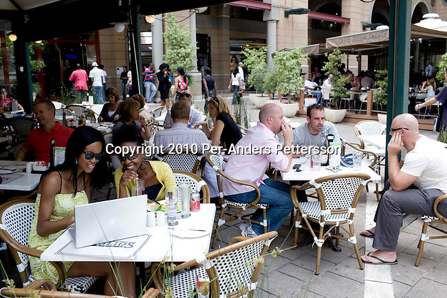 SANDTON, SOUTH AFRICA - JANUARY 16: Upmarket people eat lunch at Nelson Mandela  Square on January 16, 2010, in Johannesburg, South Africa. This is the most exclusive shopping mall in the country and some of the best  hotels and restaurants in Johannesburg. A huge bronze statue of Nelson Mandela has been placed in the square. An ever increasing black middle class and elite has more money to spend that before and this is a popular place to buy famous brands. (Photo by Per-Anders Pettersson/Getty Images)