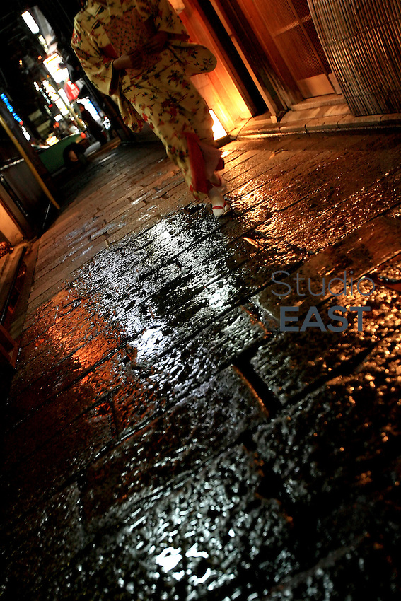 A woman in kimono walks the streets of Gion neighborhood at night in Kyoto, Japan, on November 7, 2006. Kyoto is the former imperial capital of Japan, and today houses more than 1.5 million. Photo by Lucas Schifres/Pictobank