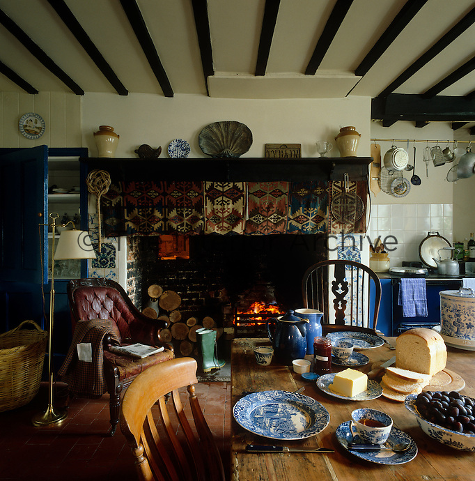 A Turkish kilim decorates the inglenook in this country kitchen in which the scrubbed wooden table is laid for breakfast