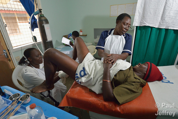 Nurse Moureen Mbise comforts Sherida Katibu as Nurse Joyce Agutu uses a cryoprobe to do cervical cryotherapy on her in the Shirati Hospital in Shirati, Tanzania. Nurse Elizabeth Peter does paperwork in the background.